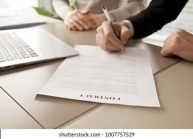 Close up image of paper contract document lying at work desk with laptop, businessman putting his signature under text of financial agreement with ballpoint pen in presence of female business partner