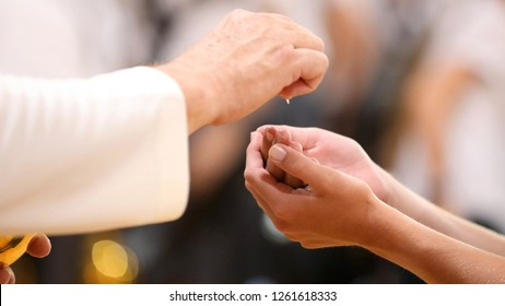 Close up image of a parishioners hands clasped receiving the bread during holy communion from a catholic priest at Mass. Religion concept, with blurred background