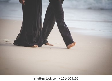 Close up image of people wearing formal clothing and walking barefoot on the beach