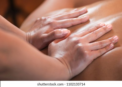 Close up image of physiotherapist massaging female patient with injured back muscle. Sports injury treatment.