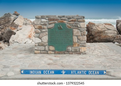 Close up image of the plaque marking the Southern most point of the African continent, Cape Agulhas in South Africa, landmark marking the meeting point of the Atlantic and Indian Ocean with blue sky