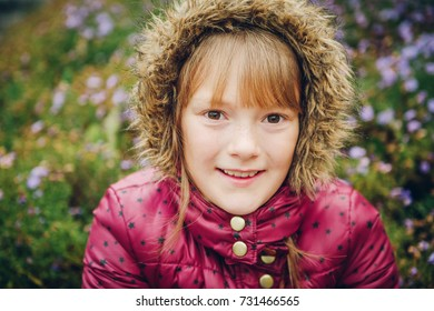 Close up image of pretty little girl wearing warm winter jacket with hood