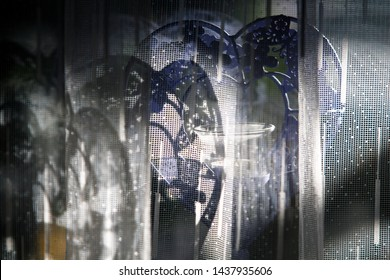 Close up image of a purple colored heart-shaped candleholder with an unlit candle behind a net curtain and under alternating lights and shadows, reminding of nice memories of an old love.
