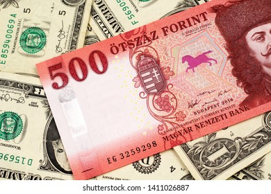 A close up image of a red Hungarian five hundred forint bank note with American one dollar bills in the background
