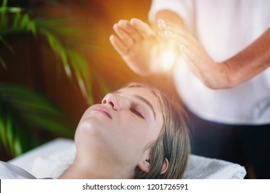 Close up image of relaxed young woman lying with her eyes closed and having Reiki healing treatment in spa center. Energy healing concept.