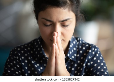 Close up image religious young indian female closed eyes praying silently with palms folded together in front of face. Believing woman ask God for miracle, morning pray, faith and superstition concept