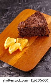 A close up image of rich chocolate cake and orange wedges on a board.