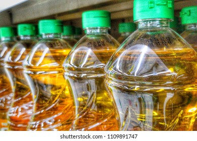 The close up image of row stack of bottles of vegetable oil on the shelves in supermarket can be sunflower, olive, palm and soy oil. its material for making the healthy or Vegan food for good health.