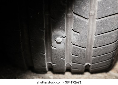 close up image of a screw nail puncturing car tire