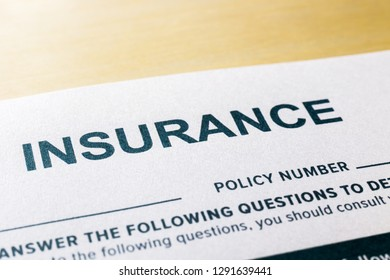 Close up image, selective focus on word INSURNCE, questionnaire and application form on wooden desk background. Healthcare, security, personal safety plan and business invesment concepts.