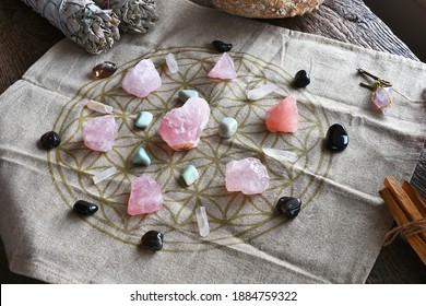 A close up image of a self love and self healing crystal grid using sacred geometry and rose quartz crystals.