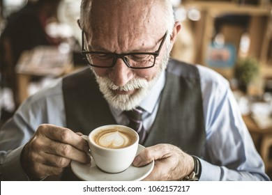 Close up image of senior businessman drinking coffee.
