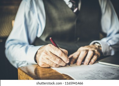 Close up image of senior businessman sign in papers.