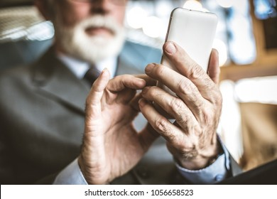 Close up image of senior businessman using mobile phone.  Focus on hand.