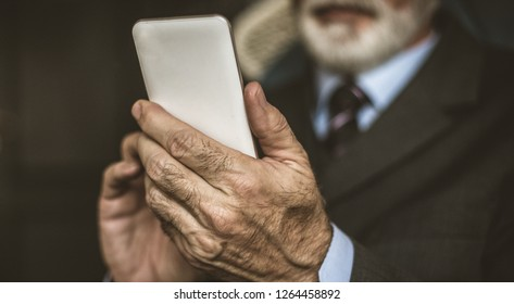 Close up image of senior businessman using smart phone.