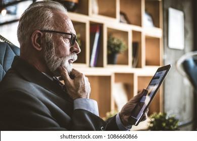 Close up image of senior man working on digital tab.