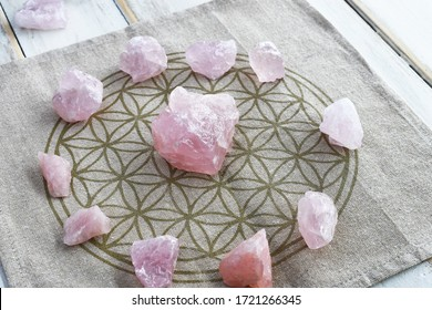 A close up image of a several rose quartz crystal in a energy healing grid using sacred geometry.
