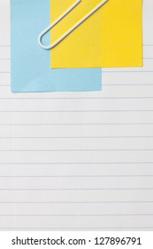 Close up image of sheet of paper with adhesive note and paper clip against white background