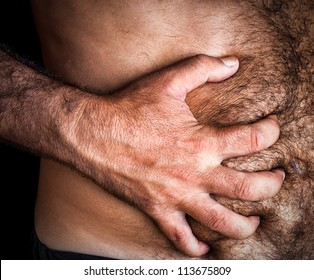 Close up image of a shirtless man suffering from severe abdominal pain