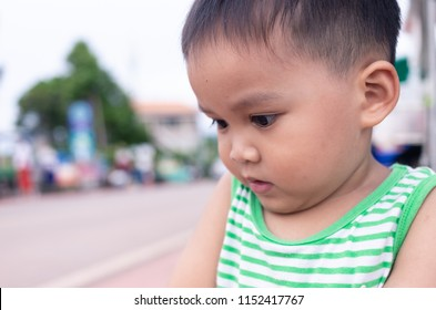 close up image of small kid standing and looking sideways