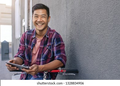 1ad3fd98e Close up image of a smiling young Asian man in a plaid shirt leaning with  his