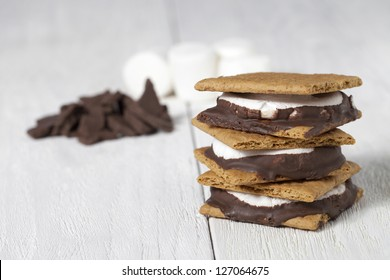 A close up image of smores sandwiches with chocolate and marshmallow on a white background