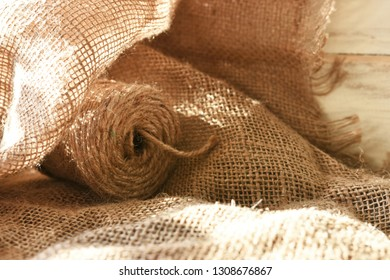 A close up image of a spool of craft twine on a burlap fabric background.
