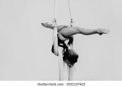 Close up image of sporty acrobatics. Hanging on silk tissue.