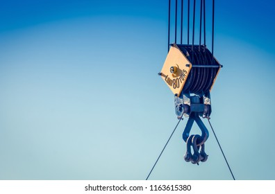 Close up image of a steel cable pulley on  a crane against a blue sky.