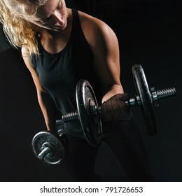 Close up image of strong blonde woman lifting weight