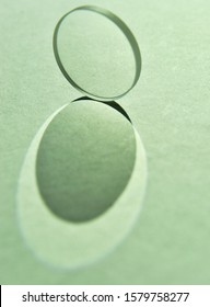 Close up image of sunlight shine through clear circular convex lens with reflection and refraction of light and cast double shade and shadow on white textured paper