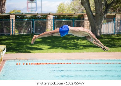 Close up image of a swimmer diving into a swimming pool during training for a big swimming race