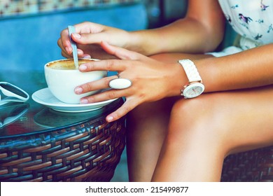 Close up image of tan stylish woman shaking her morning coffee, wearing summer trendy dress and accessorizes , siring alone at cafe. Bright colors.