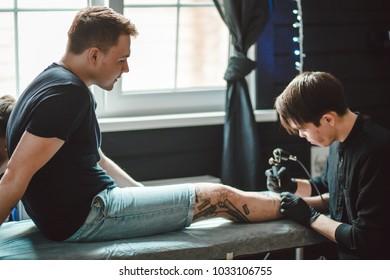 Close up image of the tattoo male artist makes a tattoo on a female leg.