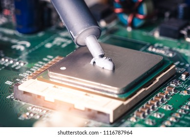 the close up image of technician squeezing the fresh thermal paste compound on the top of cpu in the socket. the concept of computer hardware, repairing, upgrade and technology.