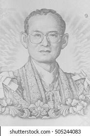 Close up image of Thai King Bhumibol Adulyadej on banknote. Thai banknote of 100 Thai baht. Black and white tone.