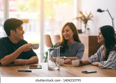 Close up image of three people enjoyed talking and drinking coffee in office
