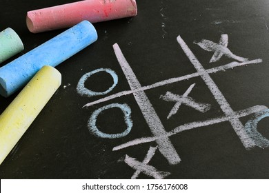 A close up image of a tic-tac-toe game done in brightly colored chalk on a black background.
