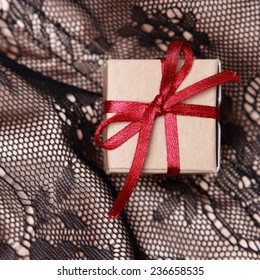 Close up image of tiny vintage gift box over Black and golden fabric with ornament pattern background on holiday theme