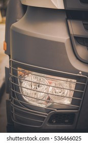 Close up image of a truck headlight with a protective grille.