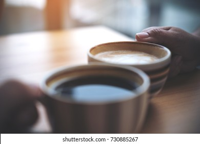 Close up image of two people clink coffee cups on wooden table in cafe