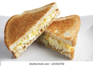 Close up image of two slices of egg salad sandwich against white background
