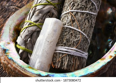 A close up image of two white sage smudge sticks with selenite crystal in an abalone shell.