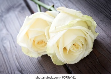 Close up image of two yellow roses on a wooden background.