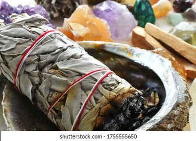 A close up image of a white sage bundle and several energy healing crystals.