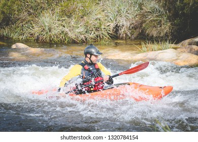 Close up image of a white water kayak paddler riding white water on a mountain river