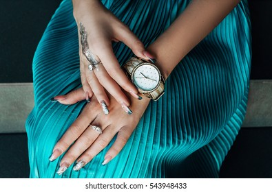 Close up image of woman hand, with stylish gold classic watches, fashion details, and Mendie.
