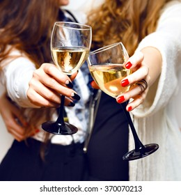 Close up image of woman hands with stylish manicure holding glasses with champagne , black and white style, party time. Cheers.