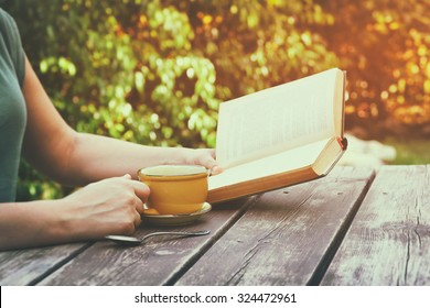 close up image of woman reading book outdoors, next to wooden table and coffe cup at afternoon. filtered image. selective focus