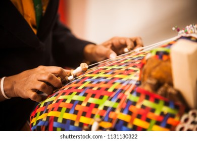 Close up image of a woman's hands weaving some cloth.